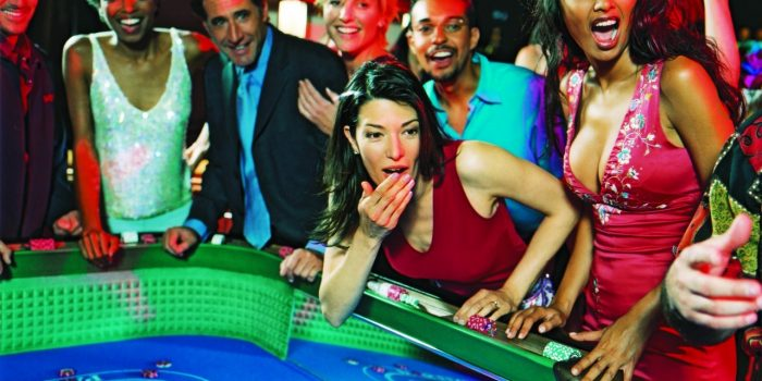 Group of People Standing Next To A Gaming Table