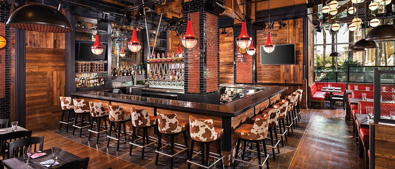 Interior Image Of Guy Fieri's Vegas Kitchen And Bar Restaurant Showing Bar Top With Cow Skin Stools And Dining Booths And Tables Area Inside The Linq Las Vegas