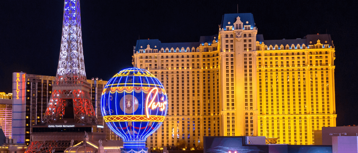 View Of Paris Hotel, Eiffel Tower, And, Hot Air Balloon At Night On The Las Vegas Strip