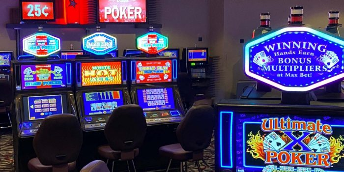 Woman Smiling Holding One Hundred Dollar Bills Sitting At A Video Poker Machine