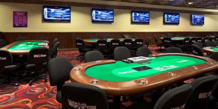 Interior Photo Of The Poker Room Showing GamingTables, Chairs, And Mounted TVs On The Wall Inside Harrah's Las Vegas