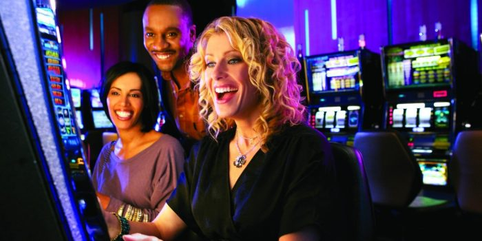 People Smiling While Playing A Slot Machine Inside Harrah's Laughlin Casino