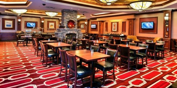 View Inside the Horseshoe Council Bluffs General Managers Club Showing Dining Tables With Chairs, Fire Place, And TV's Mounted on the Walls