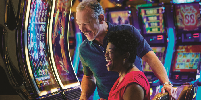 couple looking happy as they play on a slot machine