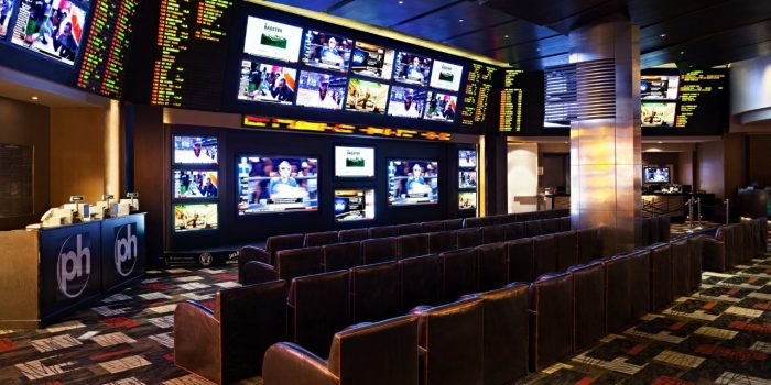 View Inside Planet Hollywood Sports Book Showing Multiple TVs, Cushioned Chairs, And Cashier Counter
