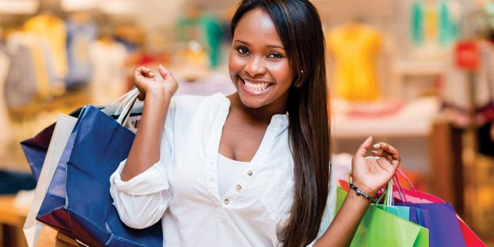 Image Of A Woman Smiling And Holding Shopping Bags