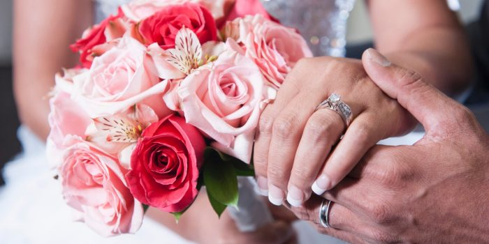 Photo Of Bride And Groom's Holding Hands Displaying Their Floral Arrangement And Wedding Rings At The Flamingo Las Vegas