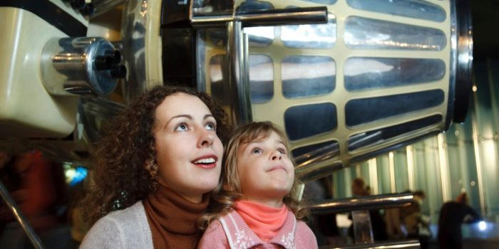 Woman and a Young Child Looking Up At Something In the Museum
