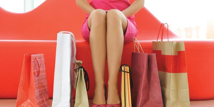 Woman In Pink Dress Sitting Next To Shopping Bags