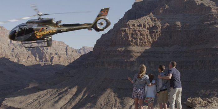 Helicopter flying into the sunset over the Grand Canyon.