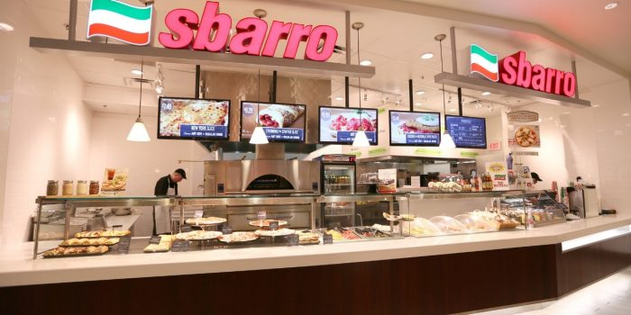 View Of Sbarro's Pizzeria Counter Showing Viewing Glasses, Cashier, And Digital Menu Options Displayed On Hanging TVs Located Inside Bally's Las Vegas