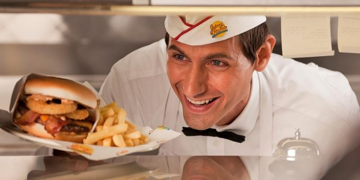 Johnny Rocket Employee Handing A Plated Cheeseburger And Fries Over The Counter Inside Caesars Windsor
