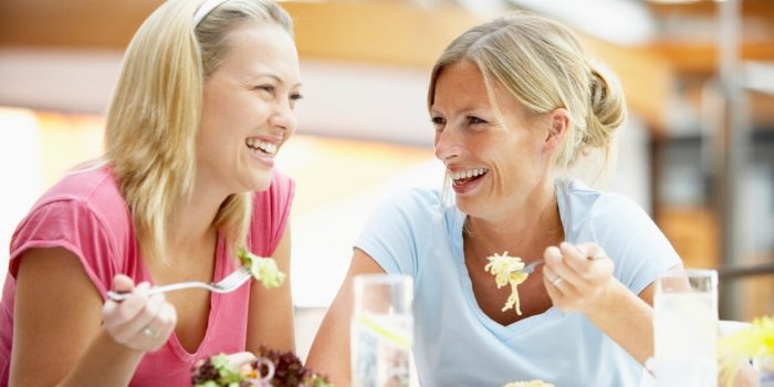 Two Women Smiling With Food On Their Plates and Holding Forks With Food