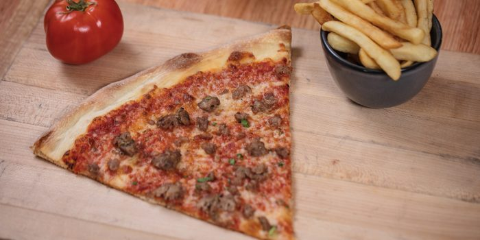 Close Up of Sausage Pizza, A Tomato, And French Fries